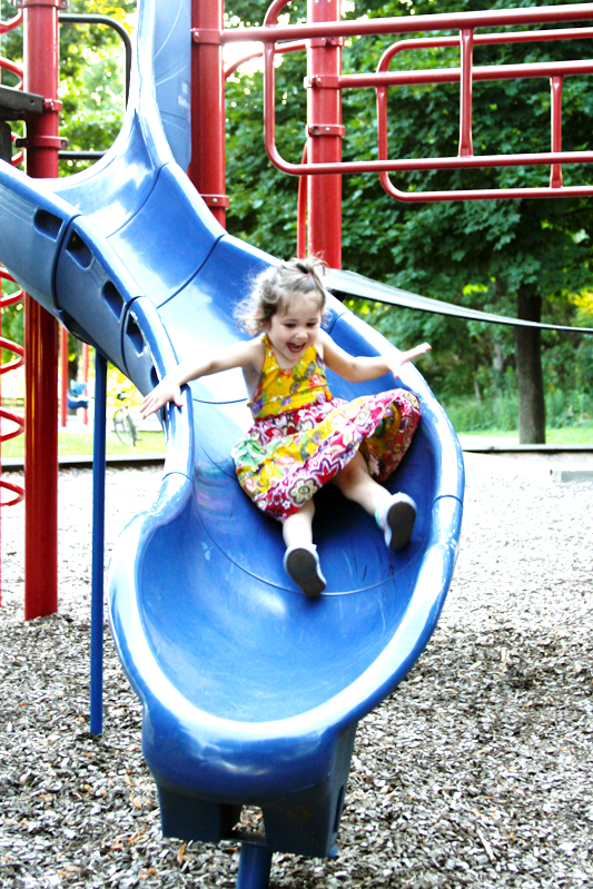 A young girl going down a slide at a local City park