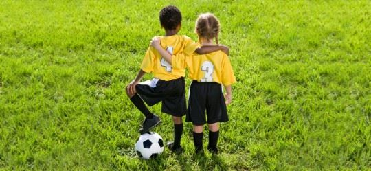 Boy and Girl Playing Soccer Together