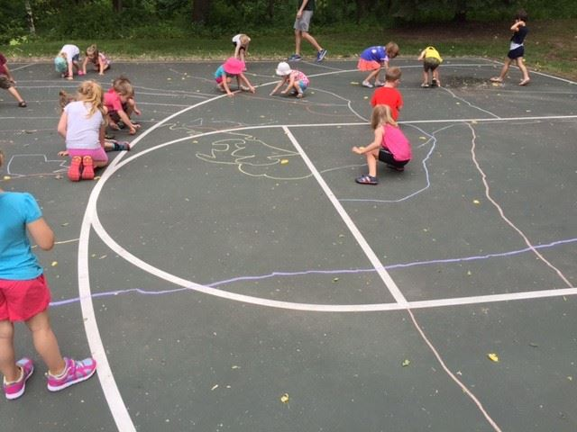 Young kids drawing with chalk on basketball court