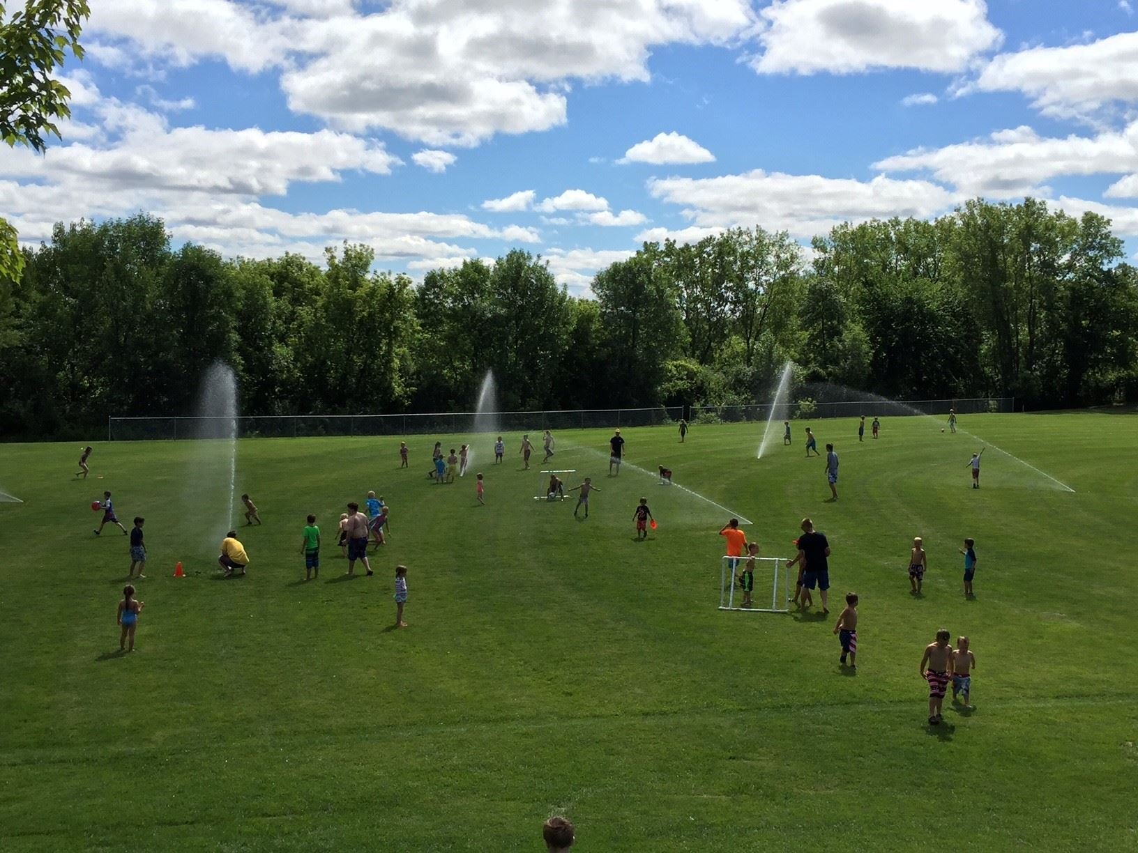Kids playing in sprinklers at Cummings