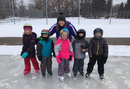 Arden Hills Ice Skating class instructor posing with young students